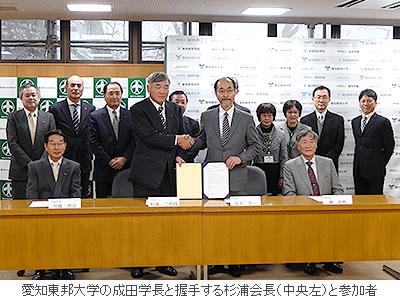 愛知東邦大学の成田学長と握手する杉浦会長(中央左)と参加者