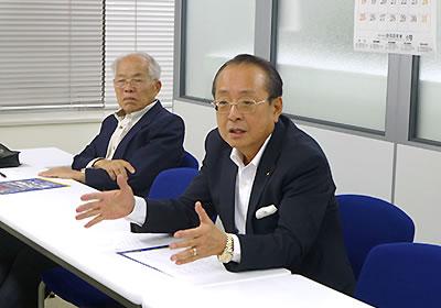 報告する村上氏(右)
